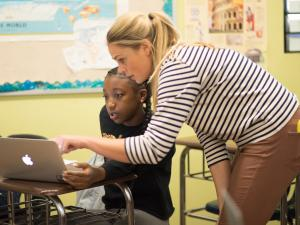 Female teacher helps a student with work on a laptop